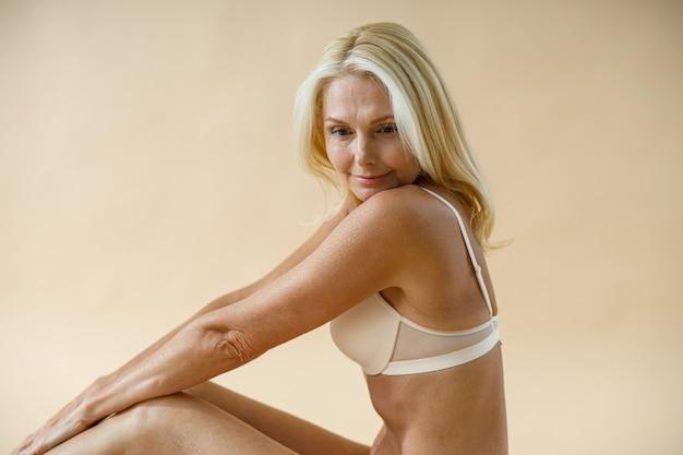 Sonhando com uma mulher loira madura em boa forma, posando de cueca, sentada no chão do estúdio e olhando