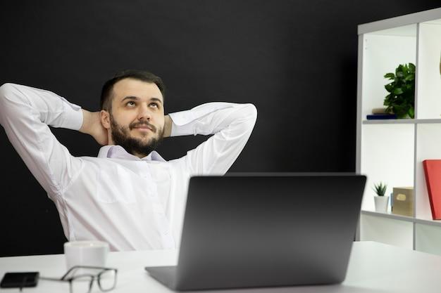 Sonhando trabalhador de escritório com as mãos na parte de trás da cabeça, olhando para cima