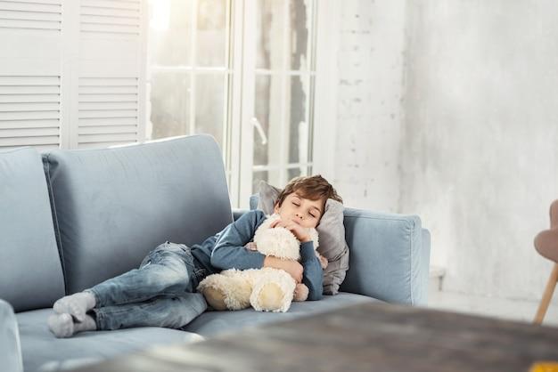 Sonhar acordado. menino fofo de cabelos louros abraçando seu brinquedo favorito e deitado no sofá confortável enquanto tira uma soneca