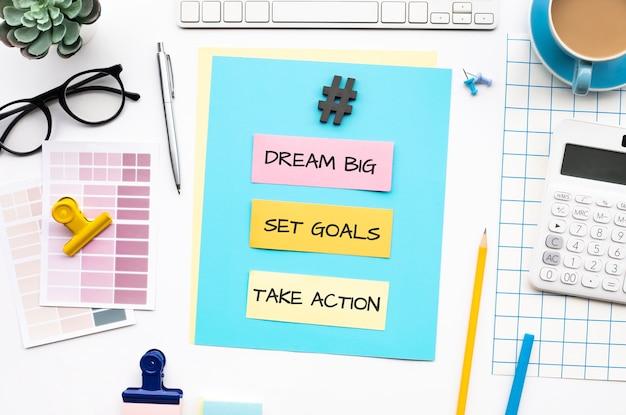 Sonhe grande, defina metas e realize conceitos de ação com texto na mesa