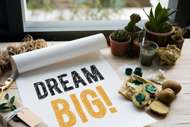Sonhe grande escrito em um papel branco e cacto