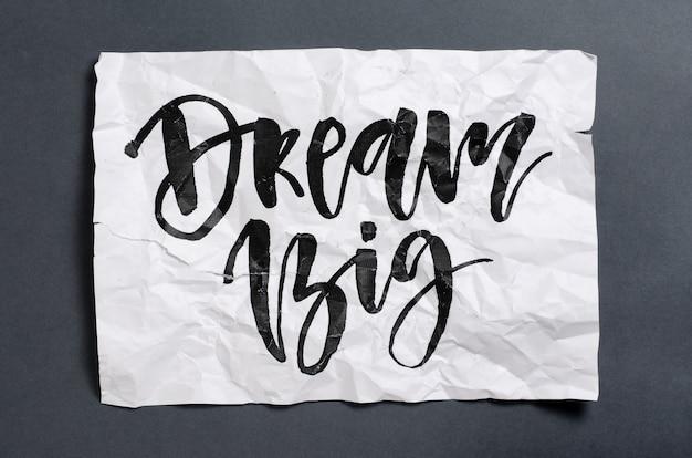 Sonhe grande. texto manuscrito em papel amassado branco. inspiração