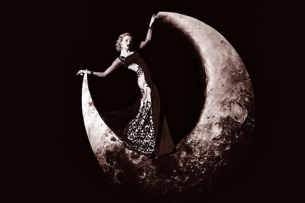 Sonho da moda. mulher jovem retrô bonita com cabelo loiro, posando na lua crescente, em um vestido elegante de noite.