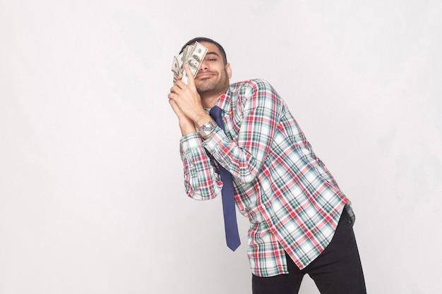 Sonho realizado! homem de negócios barbudo bonito rico satisfeito em camisa quadriculada colorida com gravata azul em pé e inclinar-se contra o fã de dinheiro na bochecha. interior, foto de estúdio, isolado em fundo cinza