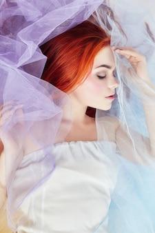 Sonhos de garota ruiva, maquiagem brilhante, pele limpa, cuidados faciais. a ruiva em um vestido colorido do ar claro encontra-se no assoalho, um close-up do retrato. mulher romântica com cabelo comprido e vestido de nuvem