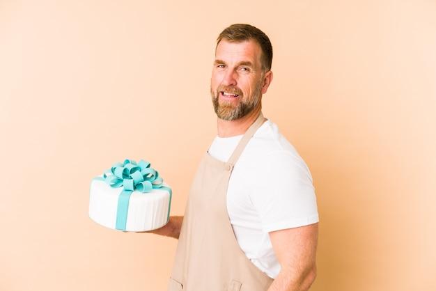 Sonior, segurando um bolo isolado no bege, olha de lado, sorridente, alegre e agradável.