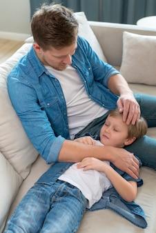 Sonolento filho descansando a cabeça nas pernas do pai