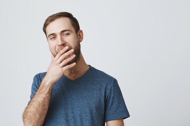 Sonolento homem barbudo bocejando, parecendo entediado
