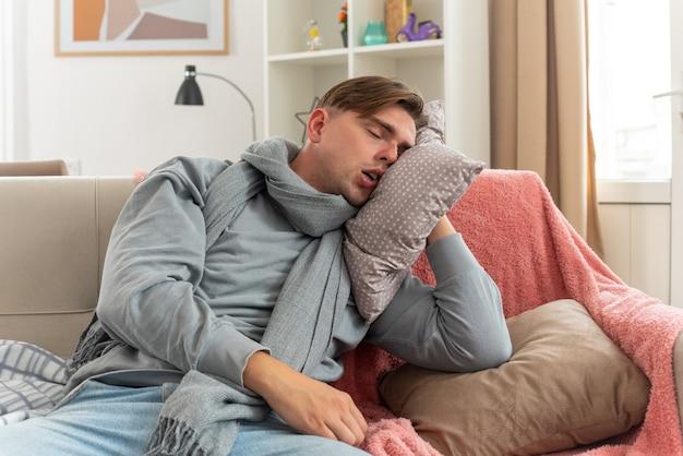 Sonolento jovem doente com um lenço no pescoço, colocando a cabeça no travesseiro, sentado no sofá da sala