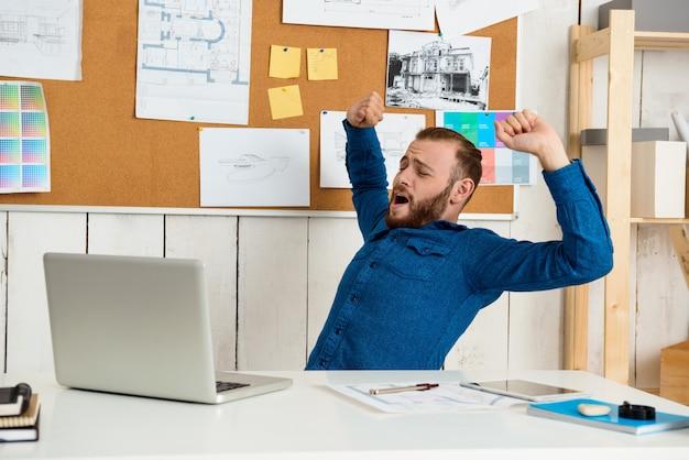 Sonolento jovem empresário de sucesso sentado no local de trabalho com computador portátil