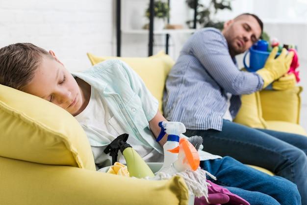 Sonolento pai e filho descansando no sofá após a limpeza