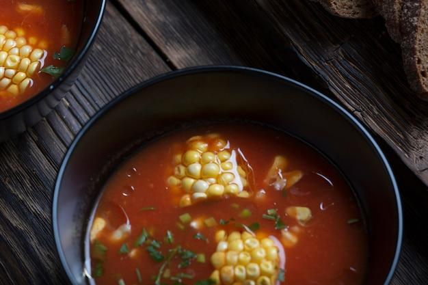 Sopa americana de milho e tomate em mesa rústica com pão de centeio