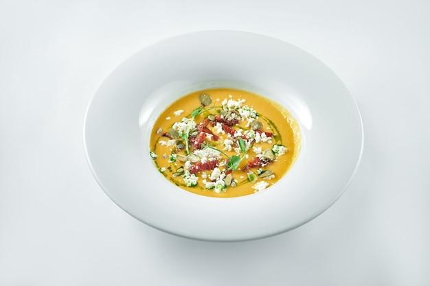 Sopa apetitosa de creme de abóbora com queijo feta, tomates secos e microgreen em um fundo branco em um prato branco