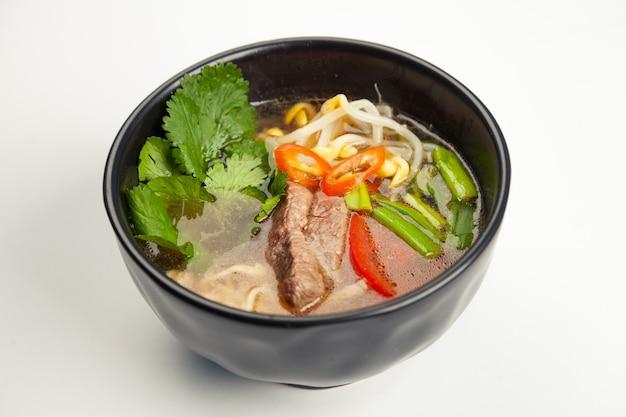 Sopa asiática com carne e macarrão udon em um careliano preto.