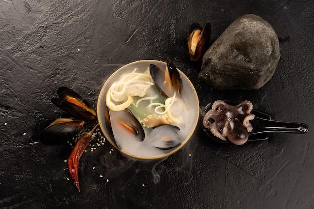 Sopa asiática de frutos do mar com mexilhões, polvo, anéis de lula, macarrão, sementes de gergelim e pimenta seca