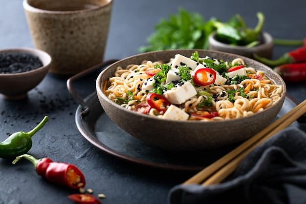 Sopa asiática de macarrão, ramen com tofu e vegetais em uma tigela de cerâmica em fundo escuro, foco seletivo