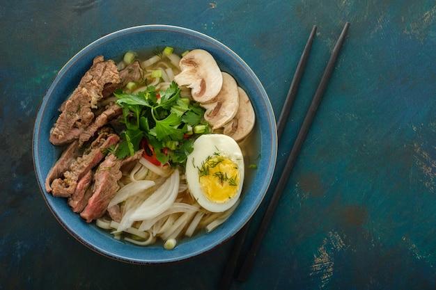 Sopa asiática de ramen com carne, ovo, cebolinha e cogumelos na tigela. vista do topo