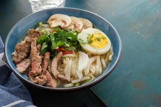 Sopa asiática de ramen com carne, ovo, cebolinha e cogumelos na tigela.
