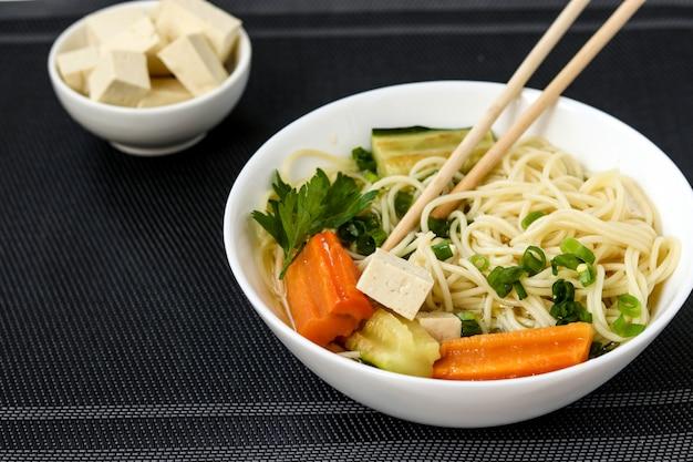 Sopa asiática tradicional com queijo tofu, macarrão, cenoura e abobrinha