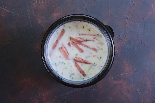 Sopa bielorrussa fria tradicional com carne de vaca, pepino, rabanete e kefir em levar o empacotamento
