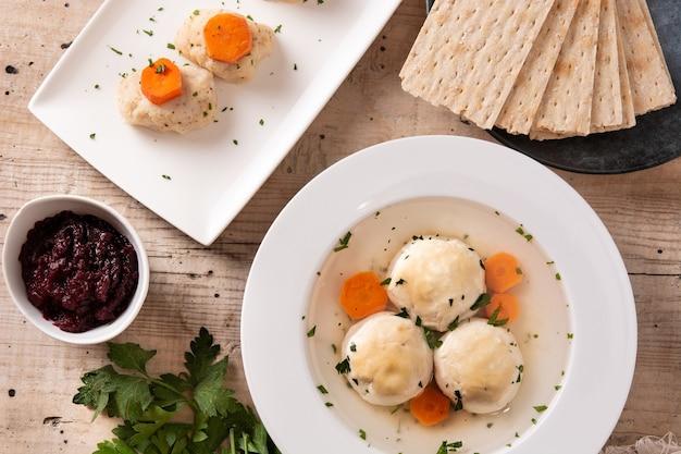 Sopa bola de matzá judaica tradicional, gefilte fish e pão matzá na mesa de madeira