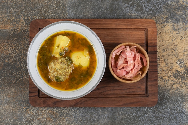 Sopa caseira com almôndegas na placa de madeira.