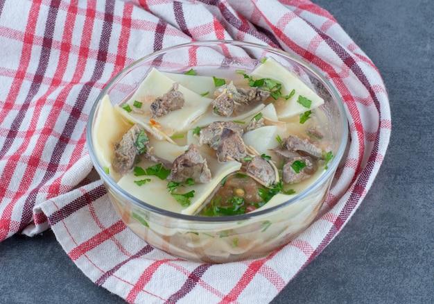 Sopa caseira com carne seca e massa em tigela de vidro.