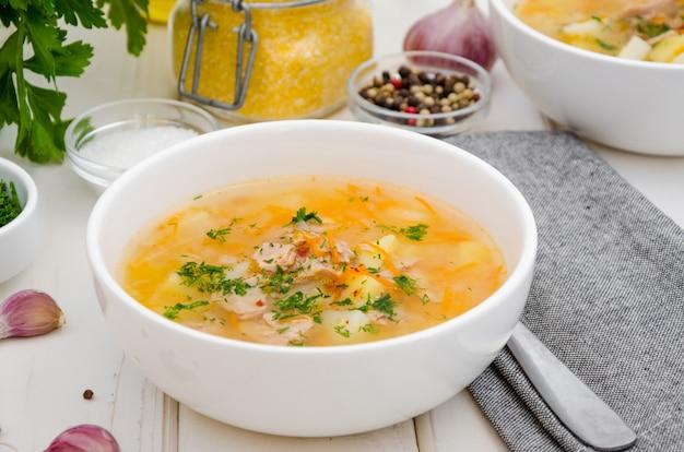 Sopa caseira com legumes, atum enlatado e grãos de milho em uma tigela sobre uma madeira branca