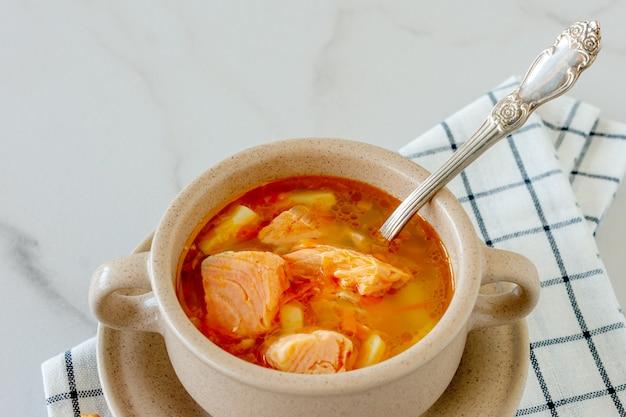 Sopa caseira com salmão com palitos de pão no mármore