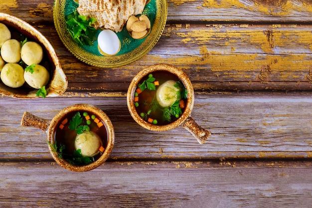 Sopa caseira de bola de matzo em dois pratos com colheres em fundo de madeira.