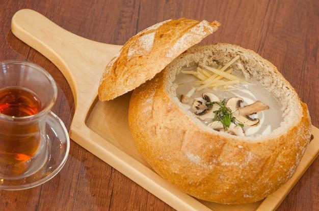 Sopa caseira de cogumelos em uma tigela de pão em uma tábua e uma xícara de chá