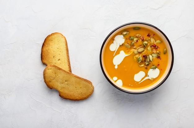 Sopa caseira de creme de abóbora de outono com creme, croutons, sementes e manjericão sobre um fundo claro de madeira.