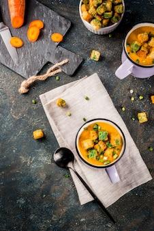 Sopa caseira de creme de cenoura em puré com bolachas de pão ervas e creme frescos em um fundo azul escuro