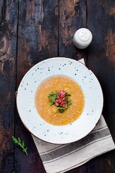 Sopa caseira de creme de lentilha vermelha com bacon e rúcula em um prato branco sobre um velho fundo de madeira