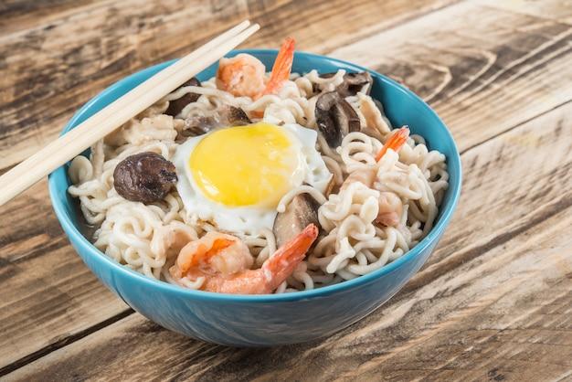 Sopa chinesa com macarrão udon, carne de porco, ovos cozidos, cogumelos e camarões close-up em uma tigela em cima da mesa