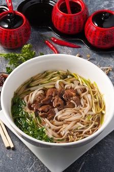 Sopa chinesa com vitela, arroz, macarrão, pepino e ervas