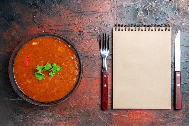 Sopa clássica de tomate em uma tigela marrom e colher com garfo, faca e caderno na mesa de cores diferentes