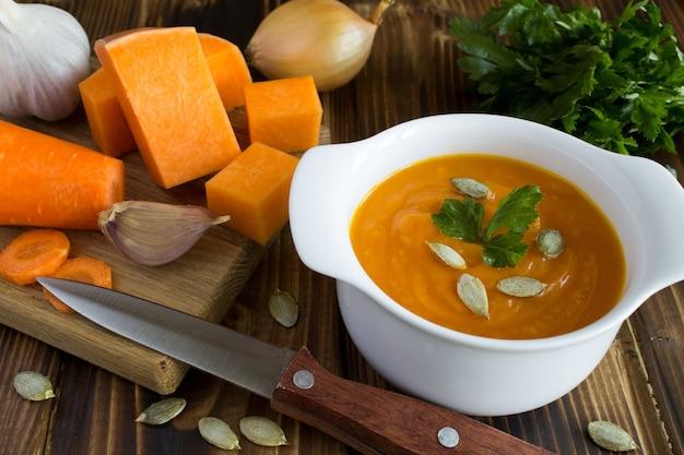 Sopa com abóbora e ingredientes no fundo de madeira