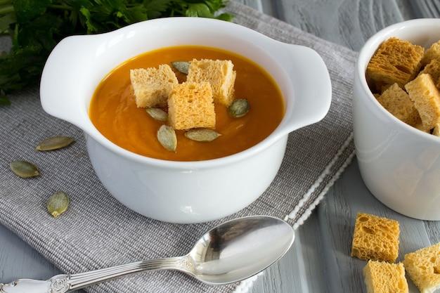 Sopa com abóbora e tostas no fundo cinza de madeira