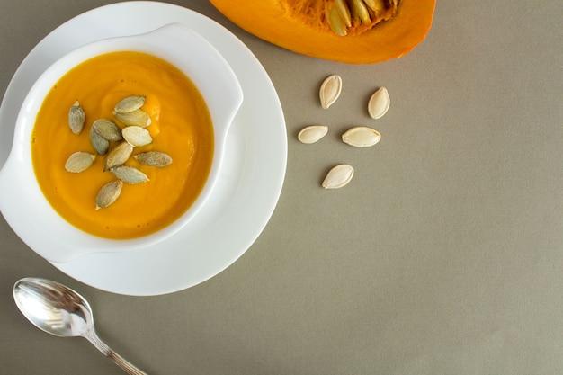 Sopa com abóbora no prato branco sobre o fundo cinza. vista superior. copie o espaço.