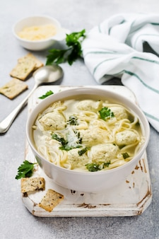 Sopa com almôndegas de frango e pasta de ovo, queijo parmesão, salsa em uma tigela de cerâmica sobre uma superfície cinza de mesa