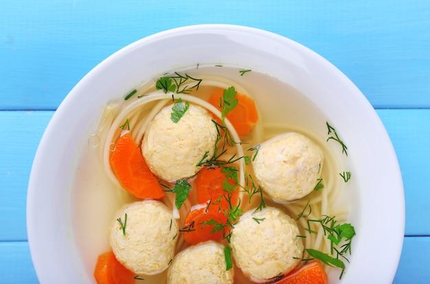 Sopa com almôndegas e macarrão em tigela de madeira