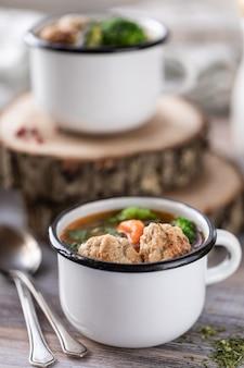 Sopa com almôndegas em canecas de metal na mesa de madeira