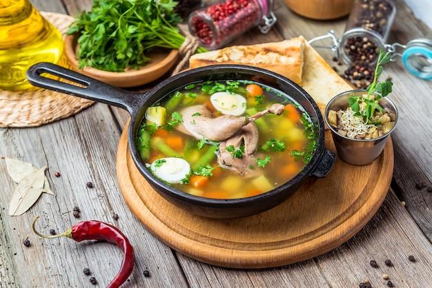 Sopa com carne de codorna, com ovos de codorna e vegetais, em uma frigideira