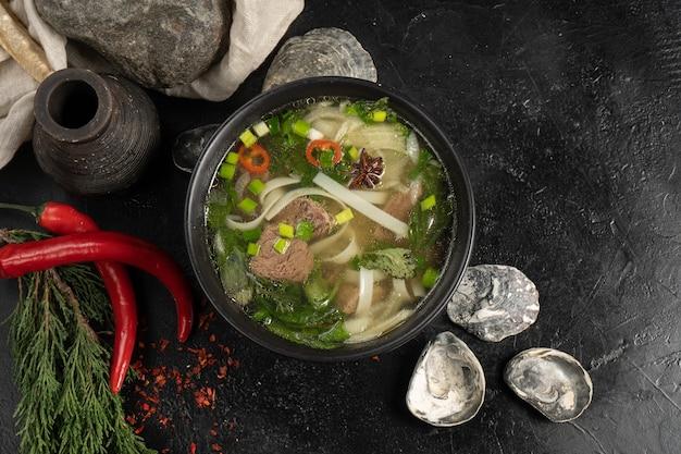 Sopa com carne, macarrão e legumes em uma mesa de cozinha de pedra escura