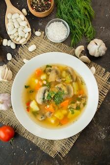 Sopa com cogumelos e ervas em um fundo escuro. prato vegetariano. prato quente. fechar-se.