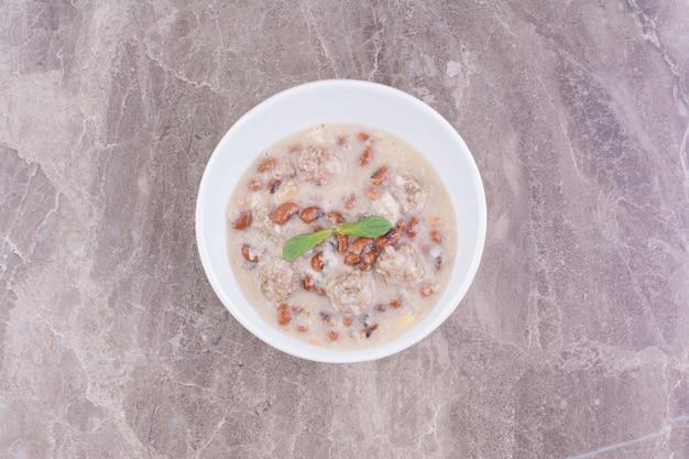 Sopa com feijão marrom e espaguete em uma xícara de cerâmica branca