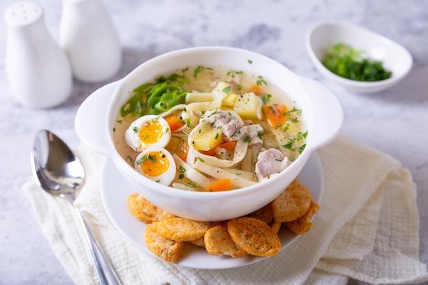 Sopa com frango, macarrão, batata, ovo de codorna e cenoura
