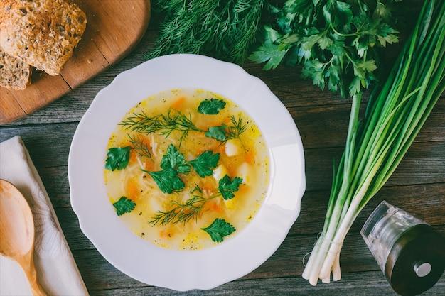 Sopa com macarrão e verduras, pão de milho e cachos de cebola, salsa e endro. vista superior closeup.