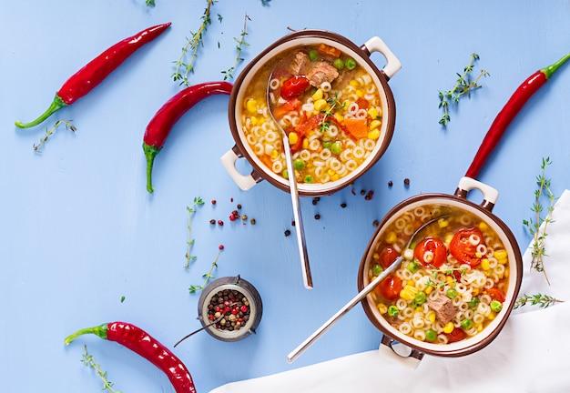 Sopa com macarrão pequeno, legumes e pedaços de carne na tigela na mesa azul. comida italiana.